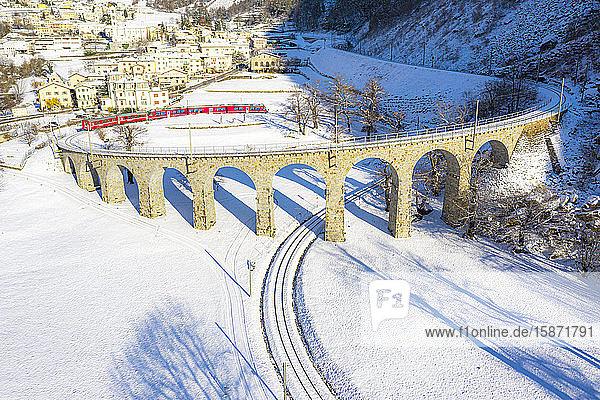 Bernina Express passes over the helical (spiral) viaduct of Brusio  UNESCO World Heritage Site  Valposchiavo  Canton of Graubunden  Switzerland  Europe
