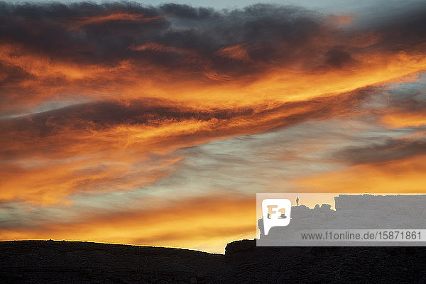 Lone figure on hill watching dramatic sunset  Ait Benhaddou  Morocco  North Africa  Africa