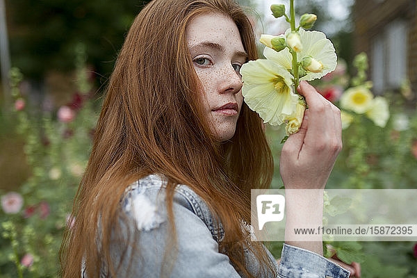 Teenage girl holding flower