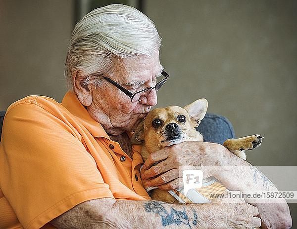 Senior Mann küsst Hund