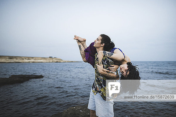 Young man carrying woman on beach