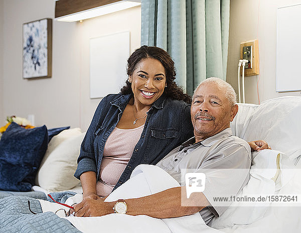 Smiling woman and senior man in bed