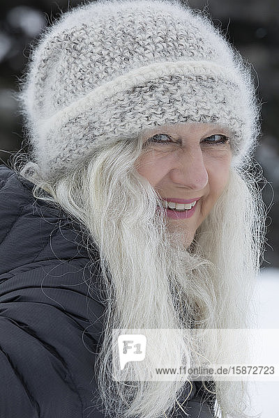 Smiling woman wearing hat in snow