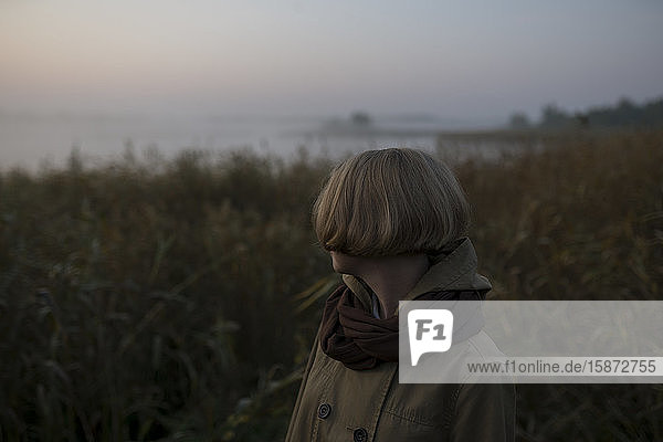 Young woman in field by lake at sunset