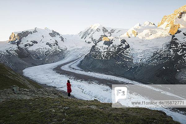 Woman standing on rock by Gorner Glacier in Valais  Switzerland