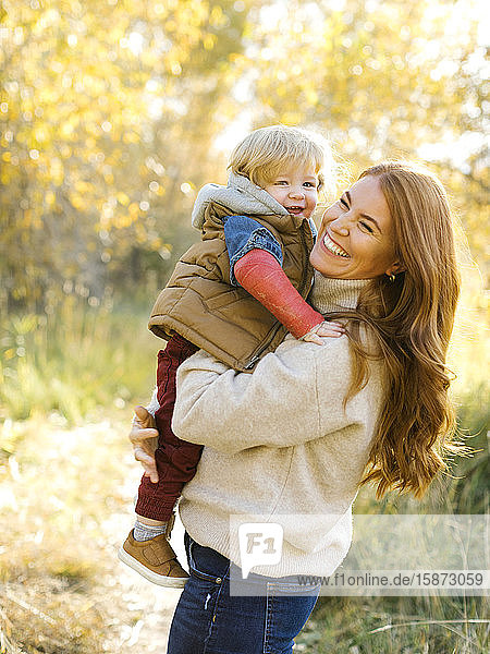 Smiling woman holding her son in forest Smiling woman holding her son in forest