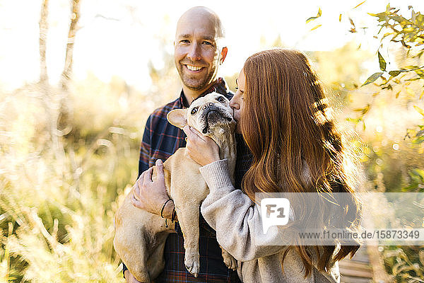Couple with pet French bulldog in forest