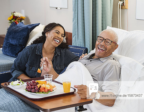 Laughing woman sitting by senior man eating fruit in bed