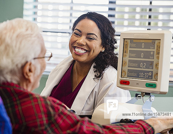 Smiling doctor and senior man by machine monitor