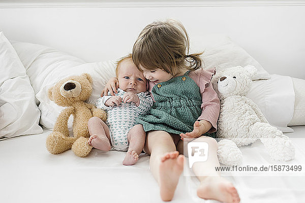 Siblings (2-5 months  2-3) sitting on bed with teddy bears
