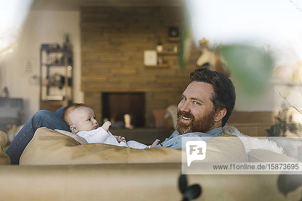 Father relaxing on sofa with baby son (2-3 months)