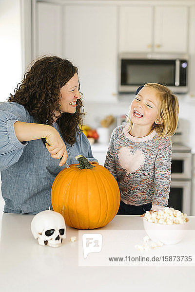 Mother and daughter carving pumpkin for Halloween Mother and daughter carving pumpkin for Halloween