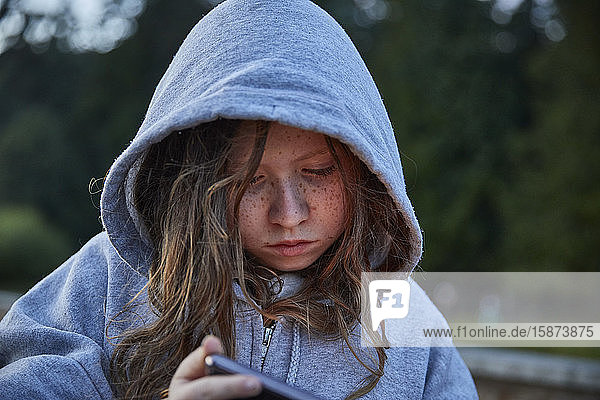 Girl in hoodie using phone