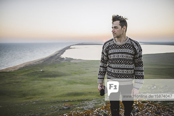 Young man in striped sweater on hill during sunset Young man in striped sweater on hill during sunset