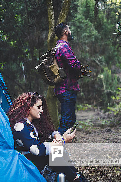 Woman sitting in tent using smart phone by man holding sticks Woman sitting in tent using smart phone by man holding sticks