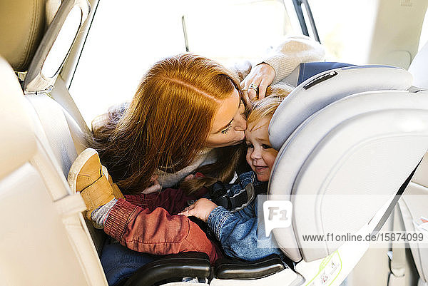 Woman kissing son in car seat