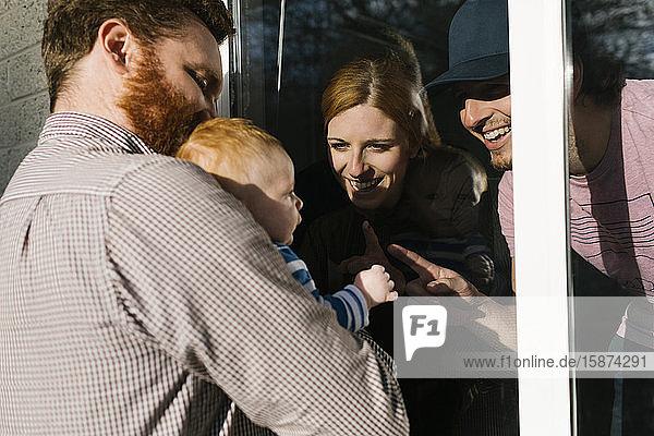 USA  Georgia  Atlanta  Man with baby son (2-5 months) visiting family through window USA, Georgia, Atlanta, Man with baby son (2-5 months) visiting family through window