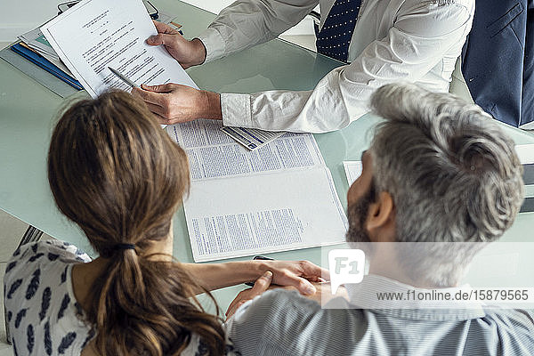 Real estate agent discussing document with couple