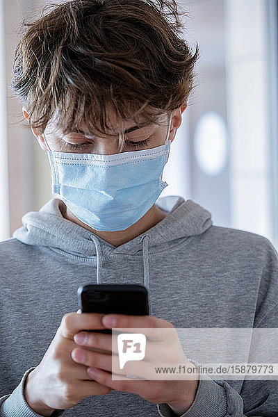 Close up of teenage boy with surgical mask using smartphone during coronavirus