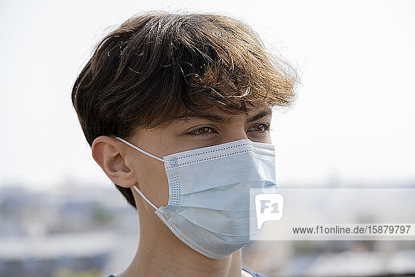 Close up of teenage boy wearing blue surgical mask outdoors