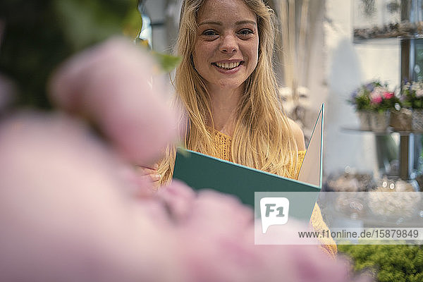 Young woman holding file in flower shop