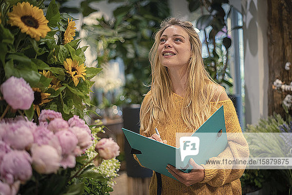Young woman writing in flower shop