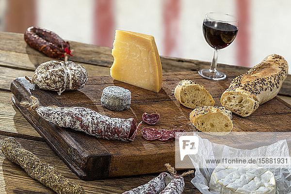 Snacks mit Wein - verschiedene Käsesorten  Feigen  Nüsse  Honig  Weintrauben  Brot auf einem grauen Hintergrund.