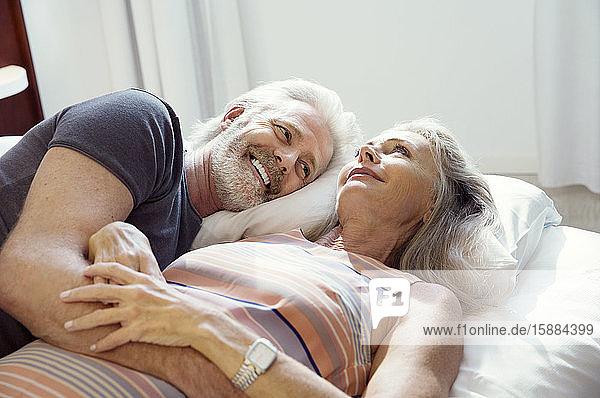 Ein Paar  das zusammen auf einem Bett liegt und lächelt.