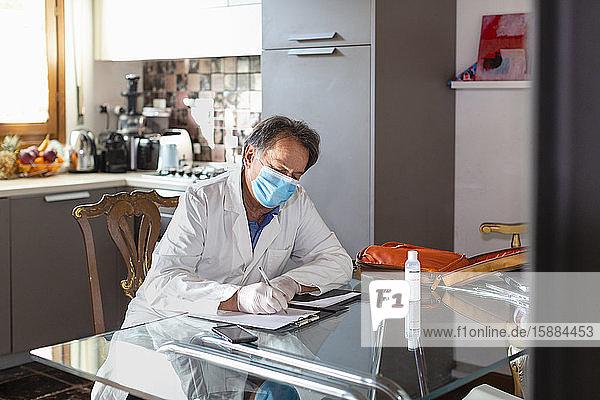 Arzt mit weißem Kittel  Gesichtsmaske und Schutzhandschuhen sitzt an einem Küchentisch und schreibt medizinische Notizen.