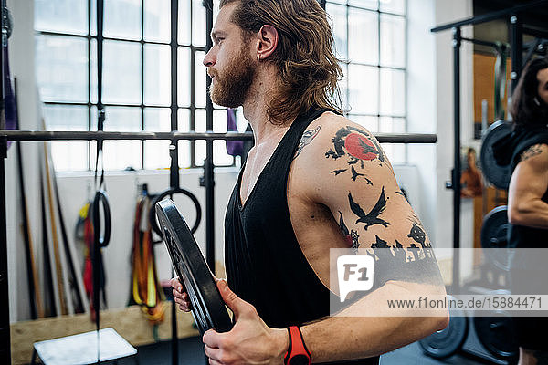 Man in a gym with tattooed arm  wearing a vest holding a weight.