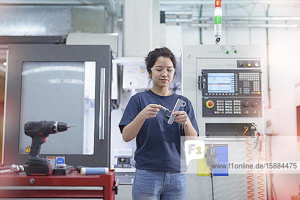 Ingenieurin  die in der Fabrik neben der CNC-Drehmaschine steht.