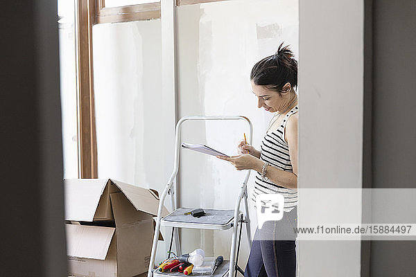 Woman looking at a pad of paper standing next to a stepladder and cardboard boxes.