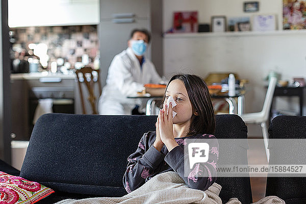 Auf einem Sofa sitzendes Mädchen  das sich die Nase putzte  und ein Arzt  der mit Gesichtsmaske und weißem Kittel in einiger Entfernung saß.