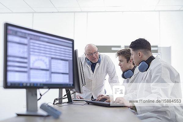 Drei männliche Wissenschaftler diskutieren über ein Windkanalexperiment in einer Forschungseinrichtung.