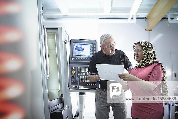Ingenieur und Designerin mit CNC-Drehbank in der Fabrik.