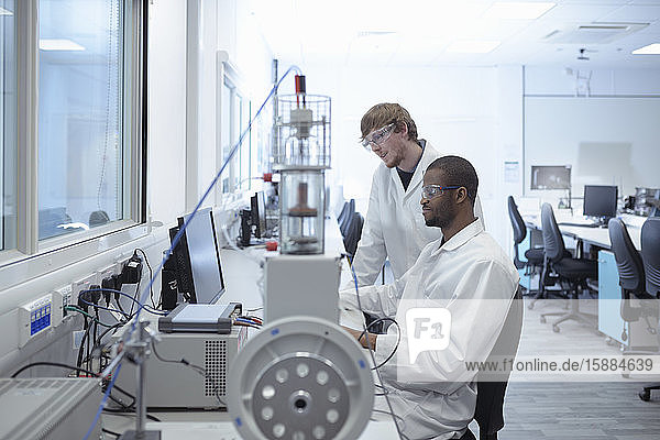 Two men wearing lab coats at a desk looking at a computer screen.