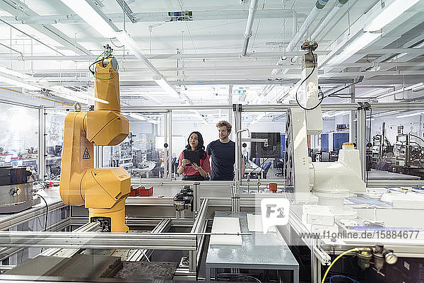 Male and female trainee engineers with robotic equipment in research facility.