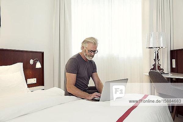 Ein Mann sitzt auf einem Bett und arbeitet an einem Laptop.