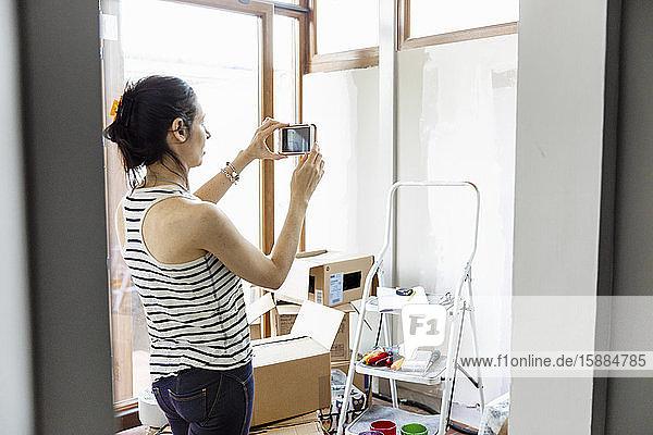 Eine Frau  die mit ihrem Mobiltelefon ein Foto macht  mit einer Trittleiter und Pappkartons im Raum.