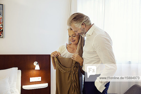 Ein Paar steht dicht nebeneinander in einem Hotelzimmer  lächelt und schaut auf ein Kleid  das die Frau in der Hand hält.
