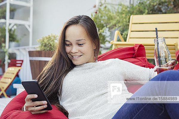 Eine Frau  die mit einer Flasche Getränk auf einem Sitzsack faulenzt und auf ein Mobiltelefon schaut.