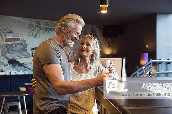 Ein Paar steht zusammen an einer Bar mit Tassen Kaffee.