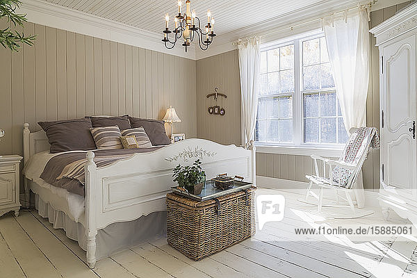 Bedroom with double bed  cream painted floorboards  brown wood panelled wall  white furniture and curtains.