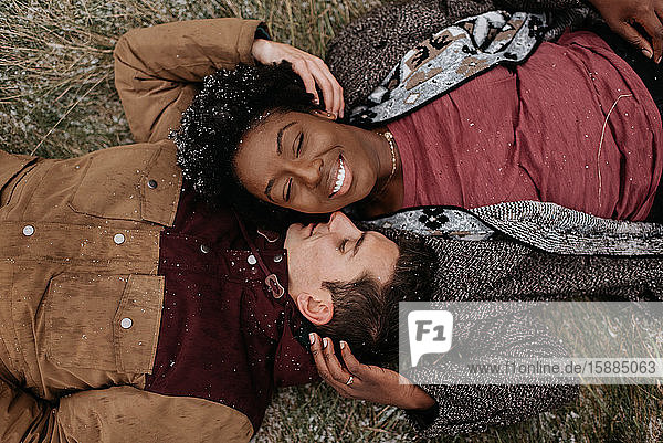 Overhead view of a black woman and white man lying on the ground with heads together  smiling.