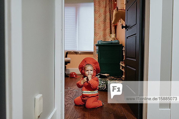 A child dressed as a firefighter kneeling on the floor.