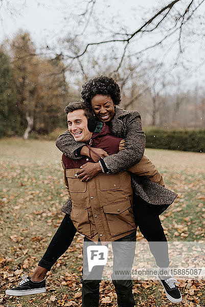 A white man giving a black woman a piggy back on a leaf strewn lawn and laughing.