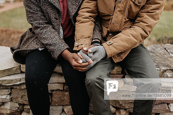 Two people holding hands  a black woman and white man seated on a wall.