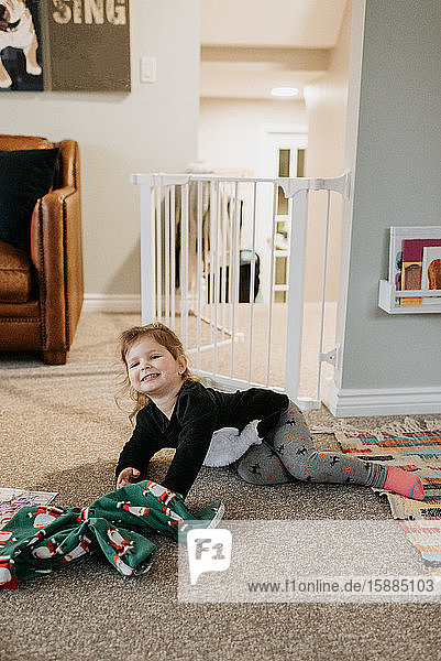 A little girl lying on the floor wearing tights and a jumper smiling at the camera.