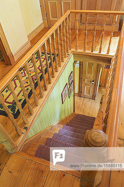 High angle view of traditional wooden staircase with red runner and wooden railing.