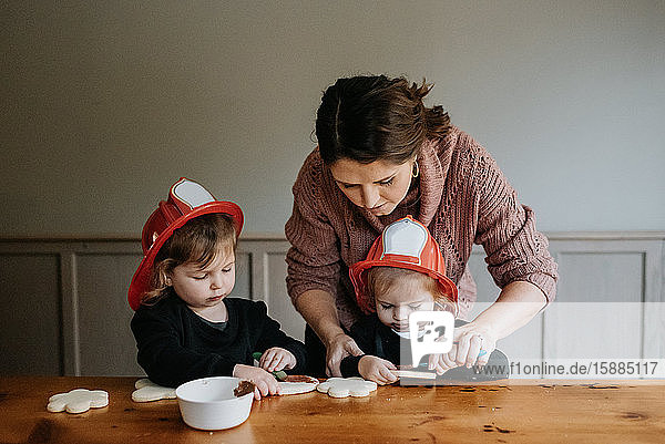 A mother helping her two children decorate cookies with chocolate.